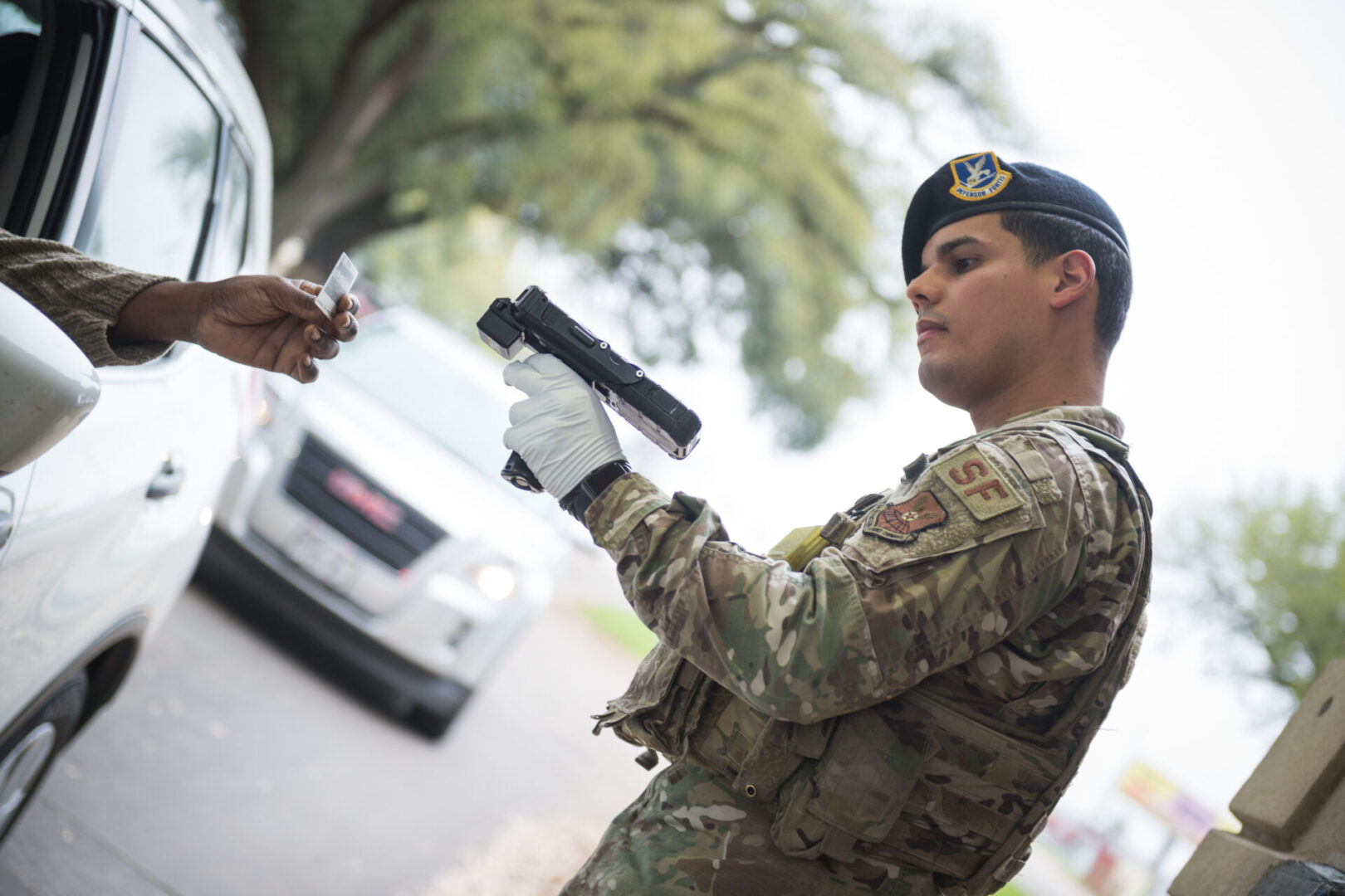 Senior Airman Abner Munoz Rios, 2nd Security Forces Squadron installation patrolman, scans an identification card at Barksdale Air Force Base, La., March 16, 2020. Due to health concerns, security forces modified entry procedures to limit interpersonal contact. (U.S. Air Force photo by Senior Airman Lillian Miller)